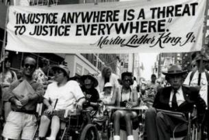 "Photo of protest with banner reading ""Injustice anywhere is a threat to justice everywhere"" - Martin Luther King, jr."